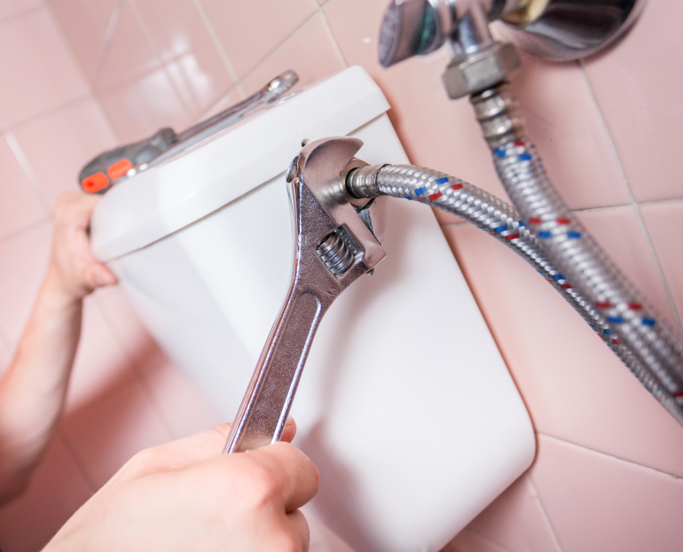 Repairman mending a toilet using a wrench