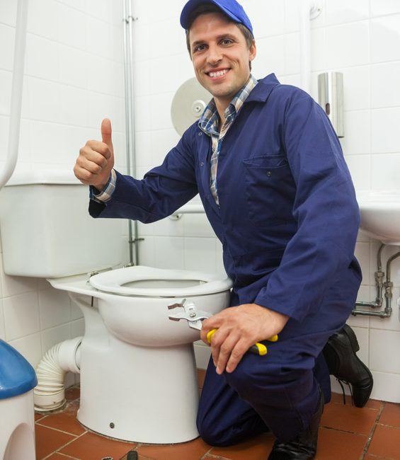 Plumber kneeling next to toilet showing thumb up in public bathroom