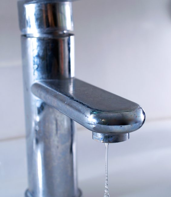 Water drops coming from an open faucet in the bathroom.