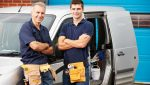 Workers In Family Business Standing Next To Van Smiling At Camera