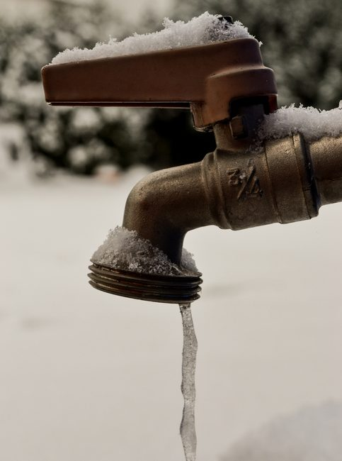 A small amount of water freezes into an icicle as it comes out of a tap, snow covers the ground in this picture. The tap has a snow covered red handle. This picture could be used to symbolize the problems with plumbing in the winter months.