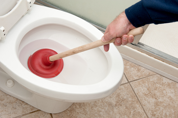 A plumber uses a plunger to unclog a toilet.