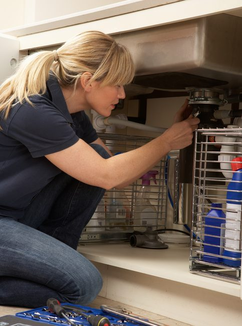 Female Plumber Working On Sink In Kitchen Kneeling Down Concentrating