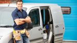Plumber Or Electrician Standing Next To Van Smiling At Camera
