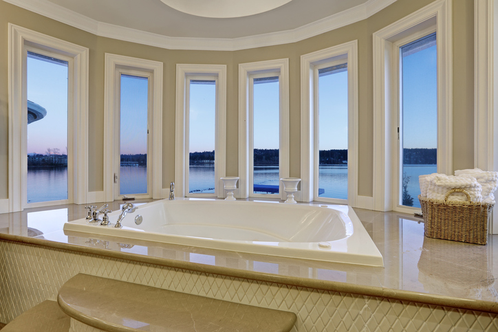 Luxurious master bathroom interior boasts jetted tub with curved windows facing the lake. Northwest, USA