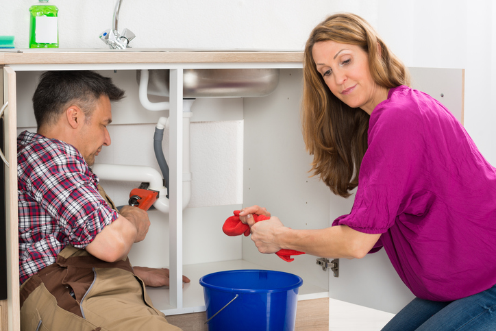 Male Plumber Repairing Pipe Under Sink While Woman Squeezing Cloth In Kitchen